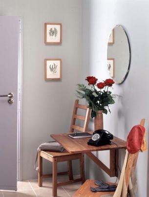 Na wolnej ścianie przedpokoju zamontowano składany drewniany stolik na telefon